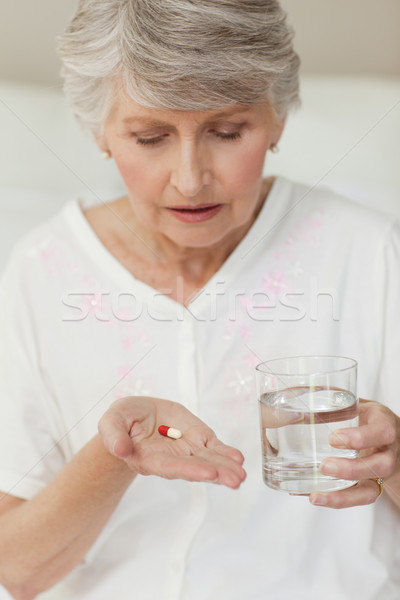 Sick senior woman taking her pills at home Stock photo © wavebreak_media