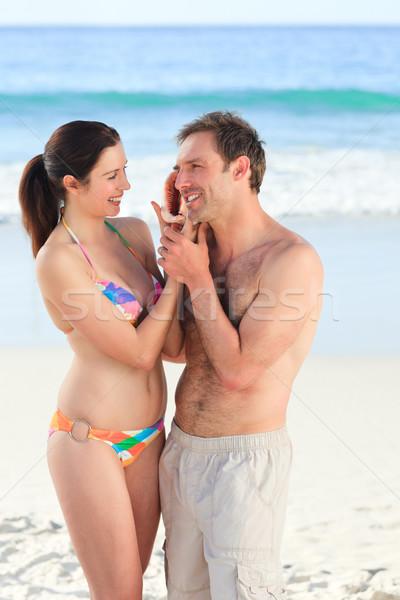 Pareja escuchar Shell manos feliz mar Foto stock © wavebreak_media