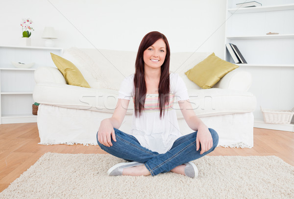Beautiful red-haired female posing while sitting on a carpet in the living room Stock photo © wavebreak_media