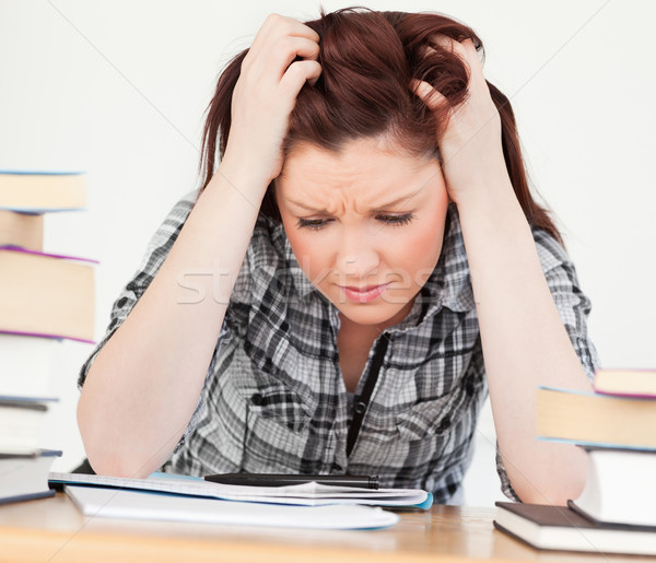 Gorgeous red-haired girl being upset while studying for an examination at her desk Stock photo © wavebreak_media
