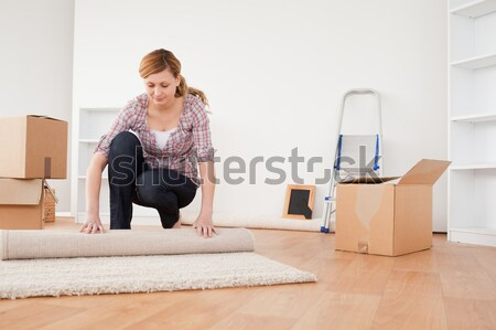 dark-haired woman seating on a carpet in the middle of a room Stock photo © wavebreak_media