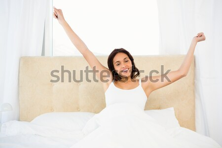 Good looking red-haired female stretching in her bed Stock photo © wavebreak_media