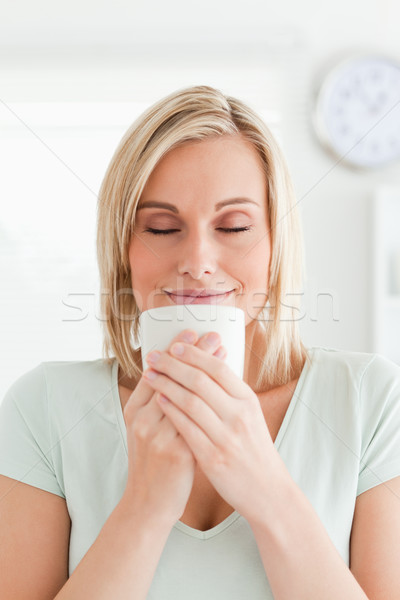 Woman taking in smell of coffee with eyes closed in the kitchen Stock photo © wavebreak_media