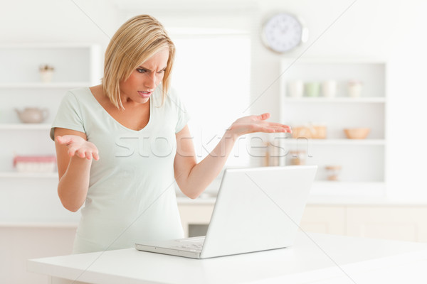 Woman looking at notebook in the kitchen without having any clue what to do  Stock photo © wavebreak_media