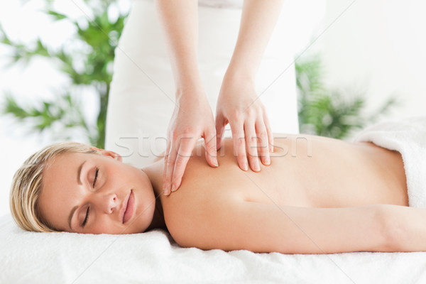 Blonde woman relaxing on a lounger during massage in a wellness center Stock photo © wavebreak_media