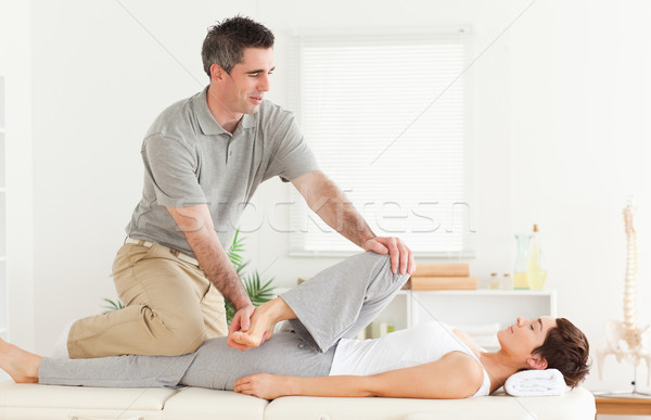 A chiropractor is stretching a female customer's leg Stock photo © wavebreak_media