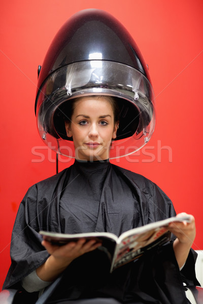 Stock photo: Portrait of a cute woman under a hairdressing machine while reading a magazine