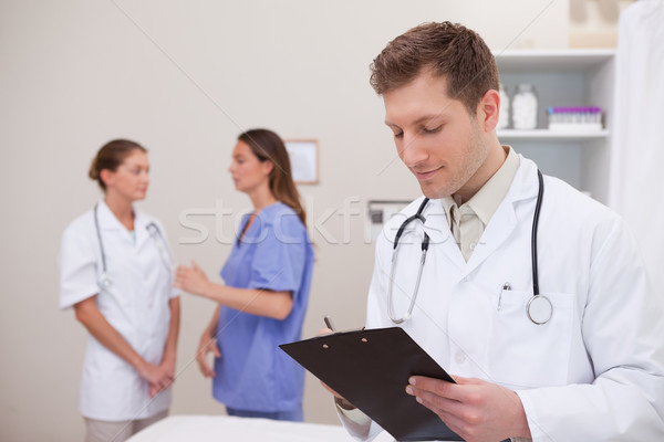 Doctor reading patients record with colleagues behind him Stock photo © wavebreak_media