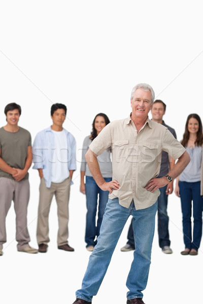 Mature man with hands on his hip and young people behind him against a white background Stock photo © wavebreak_media