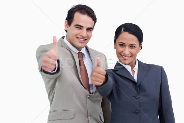 Smiling salespeople giving thumbs up against a white background Stock photo © wavebreak_media