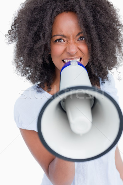 Young woman speaking loud into a megaphone against a white background Stock photo © wavebreak_media