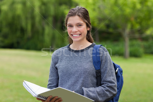 Young girl standing in a park while holding her notebook and beaming Stock photo © wavebreak_media