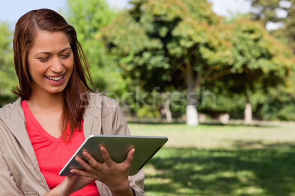 Young woman smiling enthusiastically while using a tablet in a sunny grassland area Stock photo © wavebreak_media