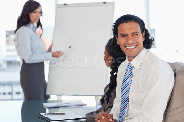 Stock photo: Smiling employee attending a presentation while his team is working behind him