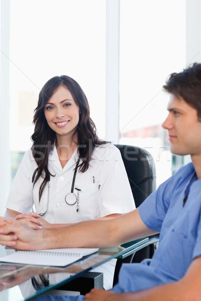восторженный женщины врач сидят столе глядя Сток-фото © wavebreak_media