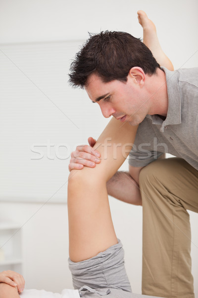 Serious osteopath holding a leg in a room Stock photo © wavebreak_media