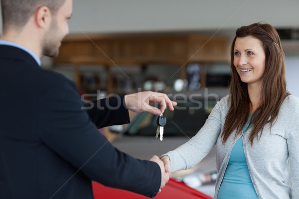 Man giving car keys while shaking hand of a woman in a garage Stock photo © wavebreak_media