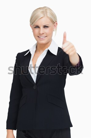 Smiling Blond Businesswoman Thumb Up Against White