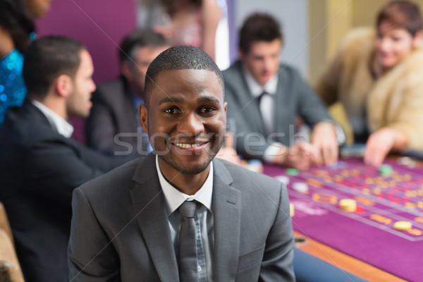 Sorridere uomo seduta casino roulette tavola Foto d'archivio © wavebreak_media