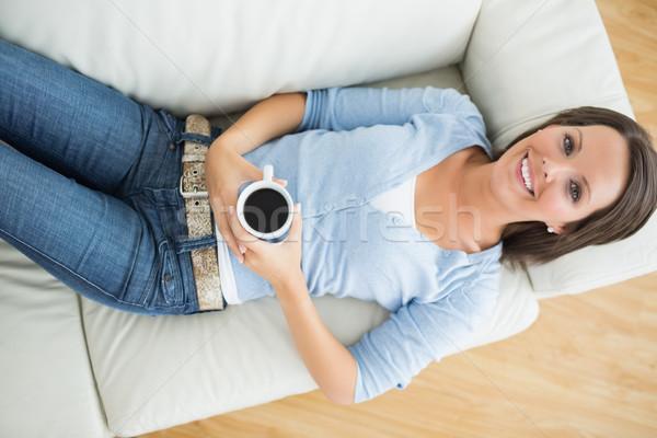 Smiling woman holding a mug of coffee on sofa in living room Stock photo © wavebreak_media