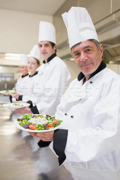 Mosolyog séfek bemutat saláta konyha étel Stock fotó © wavebreak_media