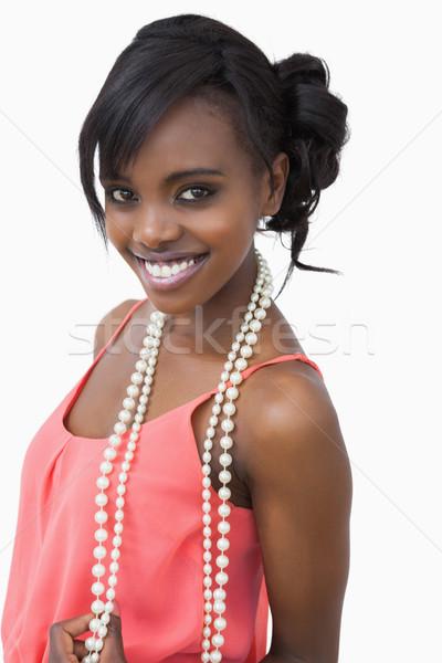 Woman wearing pink dress and pearls smiling against white background Stock photo © wavebreak_media