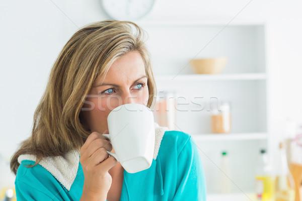 Figyelmes nő öntet talár ül konyha Stock fotó © wavebreak_media