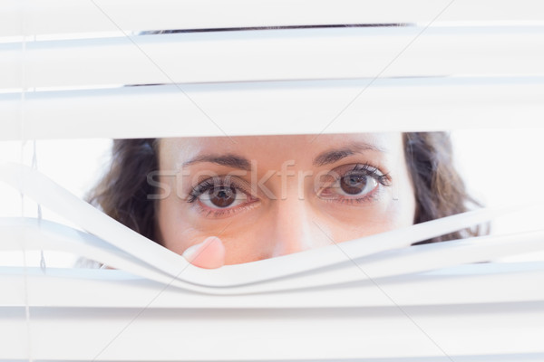 Stock photo: Curious woman looking through blinds
