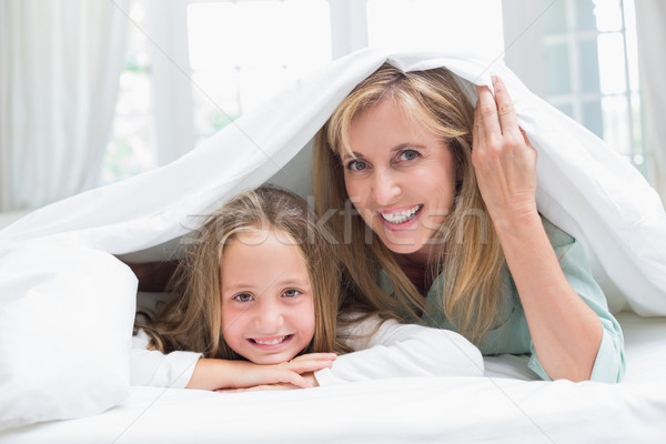 Mother and daughter looking at camera under the duvet  Stock photo © wavebreak_media