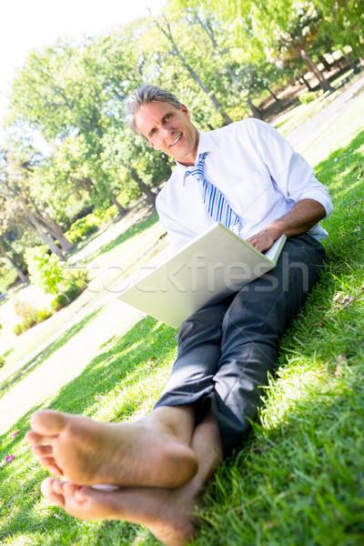 Businessman with laptop sitting on parkland Stock photo © wavebreak_media