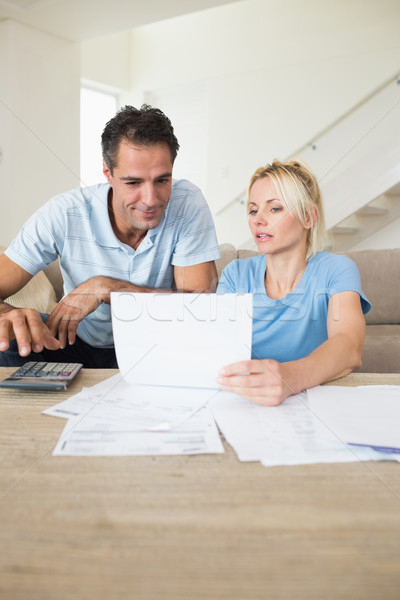 Concentrated couple with bills and calculator in living room Stock photo © wavebreak_media