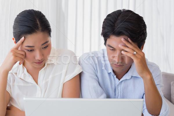 Preocupado Pareja usando la computadora portátil junto casa salón Foto stock © wavebreak_media