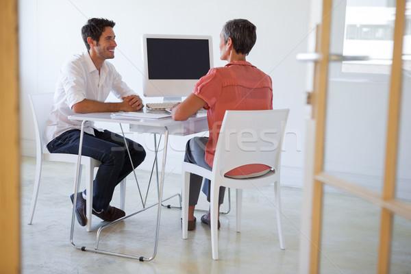 Casual pessoas de negócios falante secretária sorridente escritório Foto stock © wavebreak_media