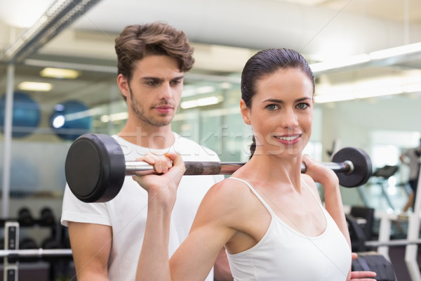 Fit smiling woman lifting barbell with her trainer Stock photo © wavebreak_media