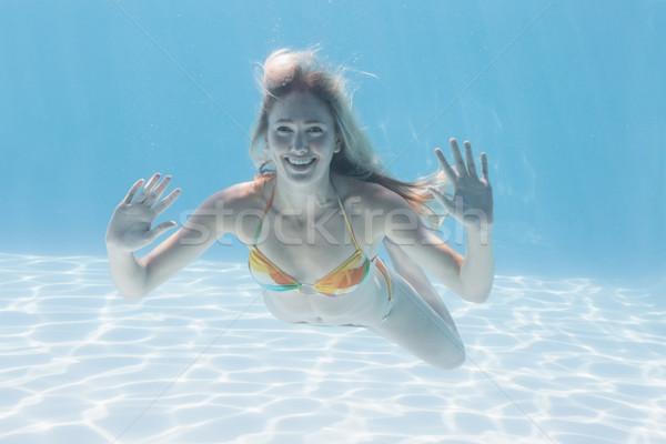 Cute blonde smiling at camera underwater in the swimming pool Stock photo © wavebreak_media