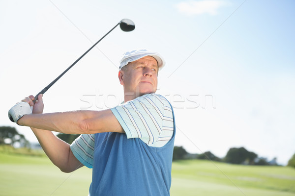 Stock photo: Concentrating golfer taking a shot