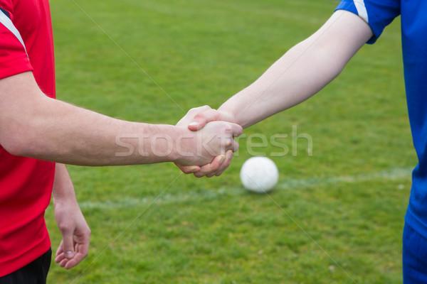 Voetbal spelers Blauw Rood handen schudden gras Stockfoto © wavebreak_media