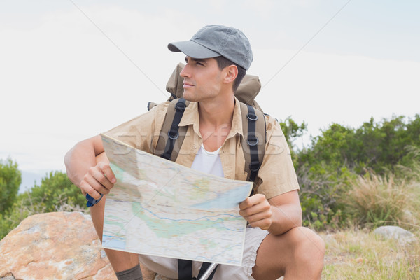 Hiking man sitting with map on mountain terrain Stock photo © wavebreak_media