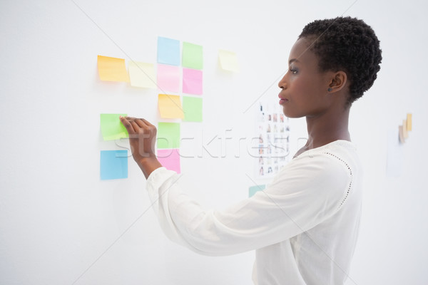 Pretty designer looking at sticky notes on window Stock photo © wavebreak_media