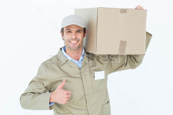 Delivery man showing thumbs up while carrying cardboard box Stock photo © wavebreak_media