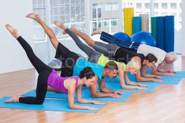 Stock photo: People exercising on fitness mats at gym