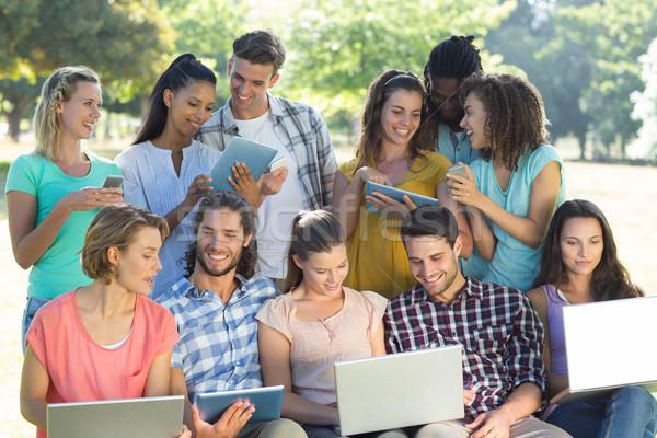 Sorridente amigos mídia dispositivos computador Foto stock © wavebreak_media