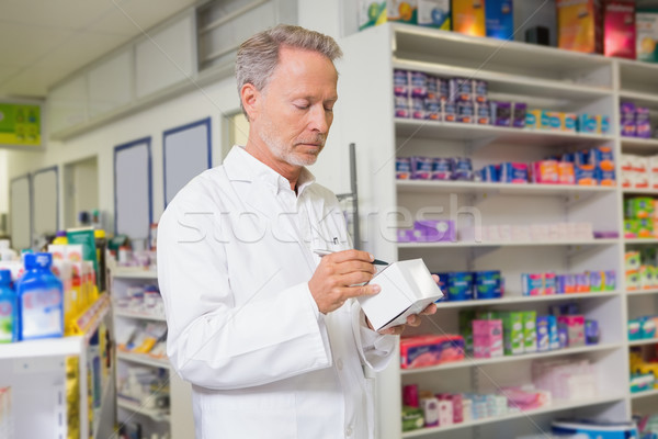 Focused pharmacist writing on box of medicine Stock photo © wavebreak_media