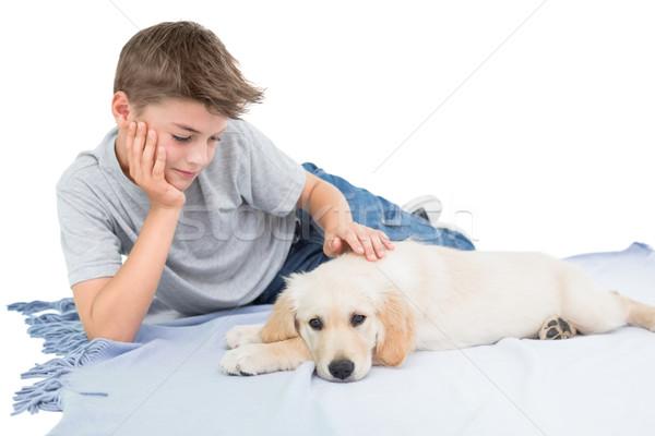 Boy stroking dog while lying on blanket Stock photo © wavebreak_media