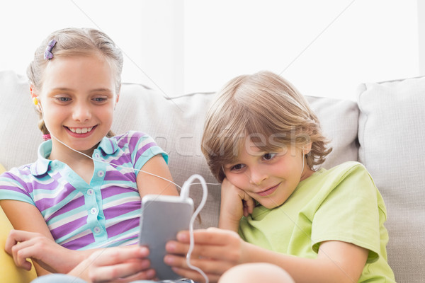 Siblings listening music through mobile phone at home Stock photo © wavebreak_media