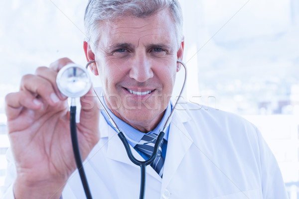 Happy doctor smiling at camera and showing his stethoscope  Stock photo © wavebreak_media