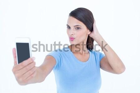 Pretty brunette taking a selfie with smartphone Stock photo © wavebreak_media