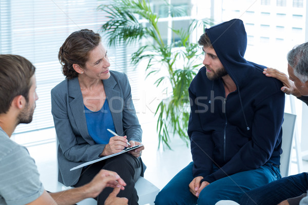 Concerned man comforting another in rehab group Stock photo © wavebreak_media