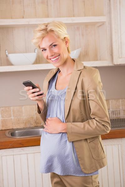 Souriant grossesse téléphone cuisine femme Photo stock © wavebreak_media