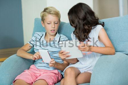Testvérek laptopot használ tabletta ül kanapé otthon Stock fotó © wavebreak_media
